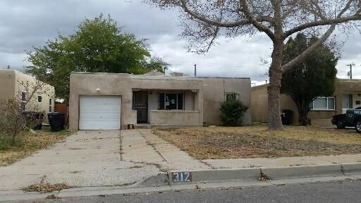 This home has potential.  Hardwood floors, plaster walls, large master suite has cozy fireplace.  Kitchen with breakfast nook, separate utility room, updated windows and heating. and 1 car garage.  Large front and back yards. Near UNM, schools and business.