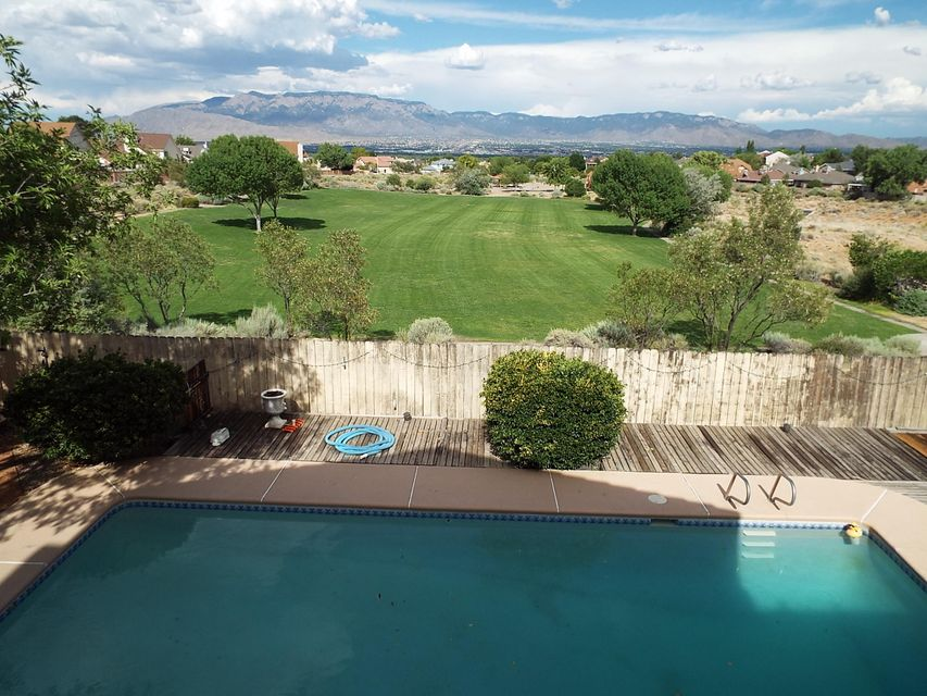 Views,Views,Views. Enjoy life with aBreathtaking Views of gorgeous Sandia Mountains and City Light views, Overlooking the inground Pool and Jacuzzi to a lush green park right out of the back yard with access.Stunning views also from upper covered deck from master bedroom  and a large concrete Patio  from outdoor Kitchen and bbq. area.Finished Basement that can be used as 2 Bedrooms or 1 master bedroom  and living area. The basement has a full bathroom.Two laundry rooms,one in the basement and the other in upper level.