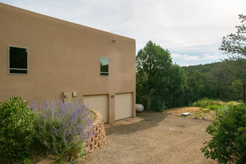 Custom home in prestigious Rancho Verde Estates. This home features 12' ceilings, plank flooring, two fireplaces, floor to ceiling windows. Gourmet kitchen with large island, granite countertops, stainless steel appliances and beautiful cabinetry. Massive covered deck offers outdoor living and views upon views of the wooded canyon and the Jemez Mountains. Huge master suite with 2-way fireplace, seating area and walk-in closet. Two large spare bedrooms located on opposite side of the house with beautiful bathroom. 4th bedroom would make a great second living area or game room. Garage has plenty of workshop/storage space and a bonus room. New Carpet in all bedrooms. Refrigerated Air and Central Vac, what more could you want? Entranosa Water. Seller would like a QUICK SALE. Bring all offers