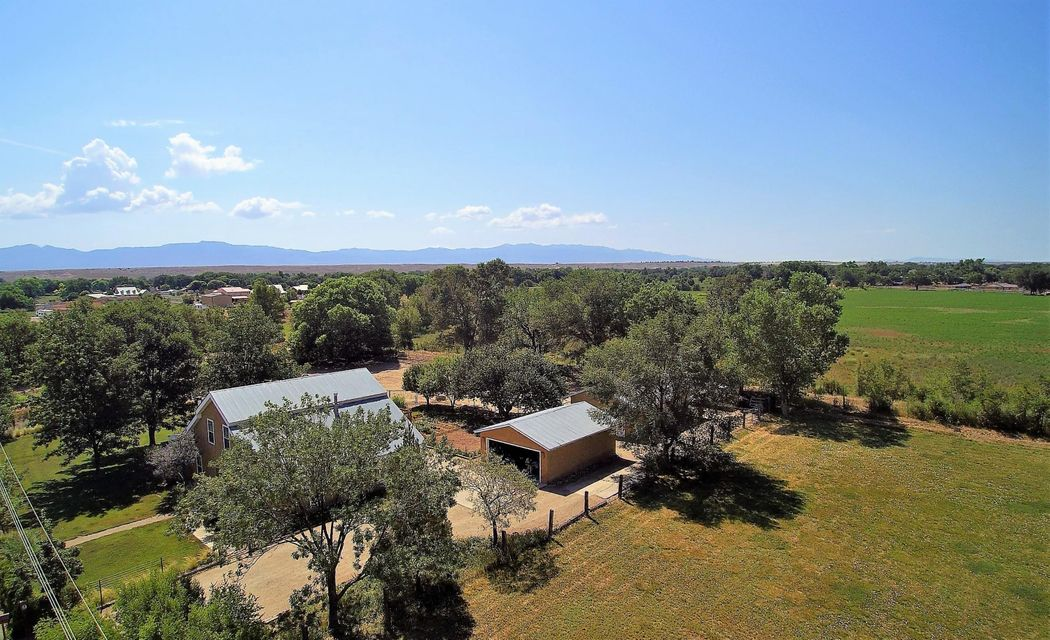 Exceptional Custom Adobe home sitting on almost 2 acres of lush Rio Grande Valley farmland. A quick 25 min. drive to downtown ABQ. Picture perfect, with brick floors on main level. Second level boasts wood floors, third bedroom, office and sitting area. Master is gracious with room for King bed, sitting area, and views of front landscape. Gaze out the kitchen's farmhouse sink window and watch your horses in their huge turnout and shed-row barn. Terrific horse property set-up, yard access to endless bosque riding. Vegetable and flower gardens right off the charming screened in back porch. Two lots included here, both have irrigation rights and there is a domestic and irrigation well for the house. Enjoy the views of the Manzano mountains.