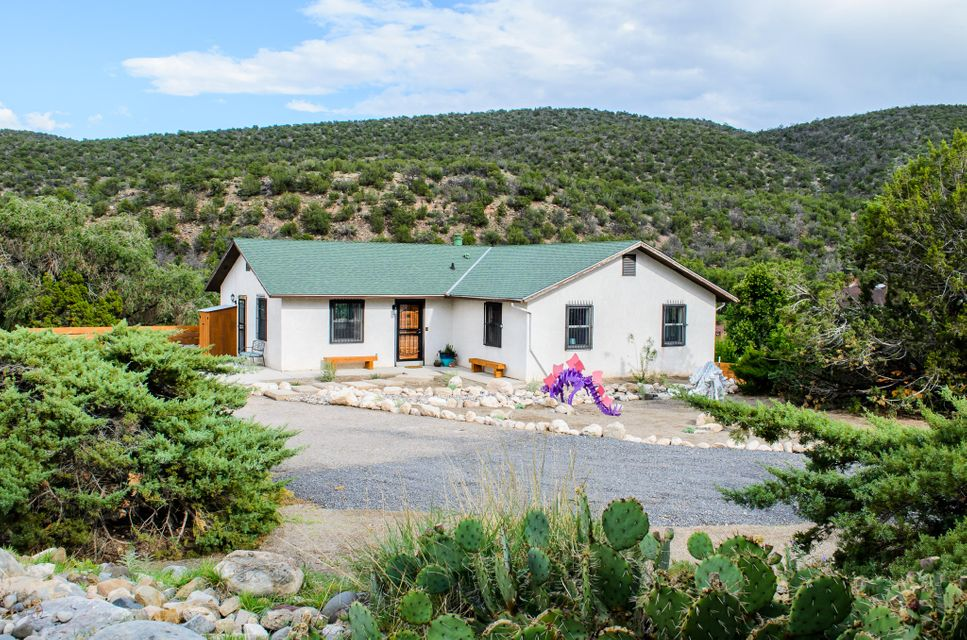 Freshly renovated home is truly move-in ready. Only 10 min to I-25!  Private setting backs to National Forest for outdoor adventures, easy trail access & stunning views of N. Sandia Peak, Capulin Peak, & Palomas Peak on custom fenced, 2.3 acres. Open floor plan is perfect for entertaining. Newly remodeled kitchen opens to large dining  & living rooms with fireplace & mountain views. Quartz counters complete the look throughout kitchen & baths. 2nd spacious living area downstairs with full bath, & billiard room, opens to patio with fire pit. 3 large bedrooms on main level, & 2 bonus rooms downstairs. Run-in shed with water & electric for horses. Separate workshop with electric is ready to be converted into a Casita. Irrigation rights. All major house systems updated including septic & well!