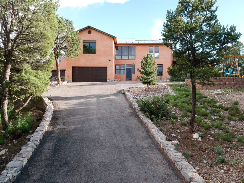 Outdoor living space abounds in this custom home with finished guest house!  This house features wood and tile floors throughout, granite counter-tops, and a stunning two-story fireplace. Enjoy the quiet of mountain living, but with the convenience of being on a paved road with easy access (15 min.) to Albuquerque. Main house is approx. 2355 sq ft and has 4 bedrooms plus an office, 2.5 baths and upstairs laundry! House has refrigerated air and central heat complimented by that amazing fireplace to keep warm. Cozy guest house is approx 1035 sq ft with full bath and kitchen and heated by a thermostat-controlled pellet stove. Property has a huge deck to relax on, a playground for kids, chicken coup, & a fenced garden area