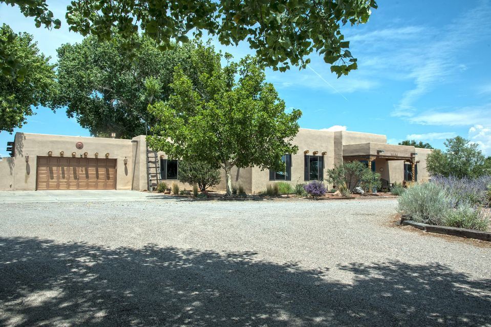 Gorgeous custom home in upscale, South Valley neighborhood. Make yourself at home on 1.25 acres of land, horse property, mature landscaping, storage shed, covered RV Parking and backyard access. Home features large great room with wood viga ceiling, pellet stove, salt cedar shutters, and fabulous brick floors. Every bedroom has its own bathroom! Gourmet kitchen with oversized gas cooktop w/griddle, and built-in oven. Stainless fridge stays! Huge office / craft or hobby room with great wood flooring. Huge master bedroom features wood viga ceiling, kiva fireplace, walk in closet, and a jetted tub. Guest home with separate entrance, kitchenette, and bath! Backyard is immaculately landscaped, enjoy your time on the huge covered patio or detached patio w/ceiling fans and misters. Private Pool.