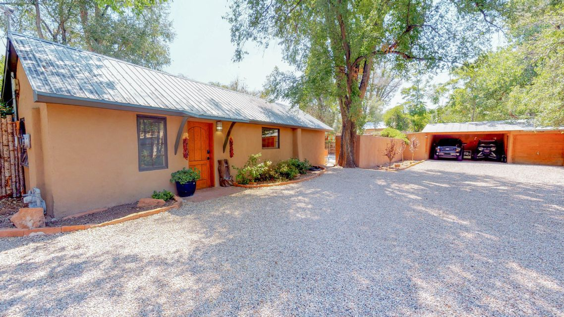 Charming New Mexican, North Valley Adobe home with Southwest charm. On lush cottonwood shaded .7 acre lot, featuring tall trees surrounded by gated private fencing, brick floors, wood-vigas ceilings, 2 Kiva fireplaces, 2 enclosed sunrooms, master bedroom is an addition! IMagine all the fun you\'ll have with the in-ground swimming pool with waterfall, pool cabana, 2 patio areas, walking distance to river trails, bike path, and fishing areas. Don\'t miss out! View it today!
