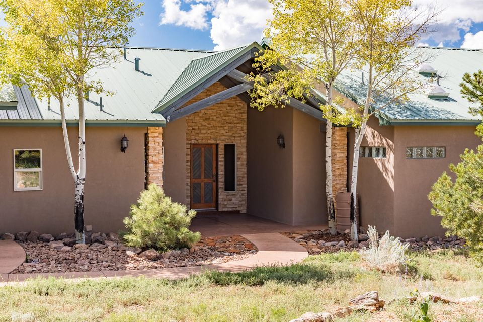 **OPEN SUN 9/24 11-1PM** Gorgeous southwest style mountain home in the desirable Woodlands subdivision. Sweeping views of the Sandias, Manzanos, and the valley from 2 maintenance free covered composite decks.  Inviting landscaped front entry w/beautiful stacked stoned and tongue & groove ceilings. Designer touches throughout this former parade home such as split open flowing floorplan, custom cabinetry, radiant in floor heat, stone countertops, stacked stone gas log fireplace, 2 dining areas, refrigerated air, spacious master suite with large jetted tub and separate his and her sinks. Two guest bedrooms w/lovely jack and jill bath plus bonus separate 4th bedroom, office space or exercise room. Stunning wooded lot, beautifully manicured for fire safety, hot tub pad, under 15 minutes to ABQ!