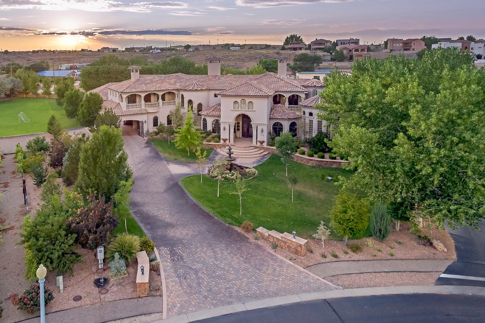 A magnificent Tuscan estate in lovely Bosque Encantado. Antique doors lead you to a grand living room, formal dining and gourmet kitchen. Separate study/library and family room. Luxurious Master Bedroom and bath on main floor. Curved Cantera stone staircase leads to the loft, recreation room and 3 bedroom suites, or you can take the elevator! Grand patio features a custom pool and spa, outdoor kitchen, bar and TV area.  Extras include: Travertine Marble floors, Media room, Wine cellar and Humidor, 4 custom fireplaces, Exercise room, private balconies and much more! Close to Award winning Twin Warriors Golf Club.  Easy access to I-25 to travel to Santa Fe.