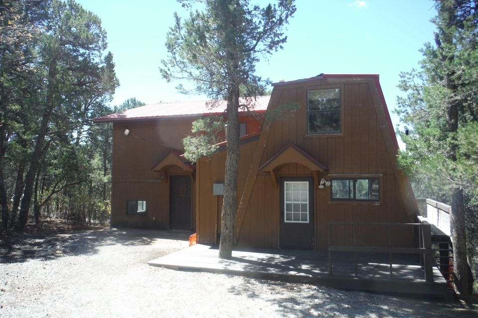 Great opportunity in the wooded parts of Tijeras. Three bedroom two bath cabin with brand new septic tank, furnace, new carpet, and fresh paint. The house offers a loft as well as a kitchen with an island, and plenty of natural light!