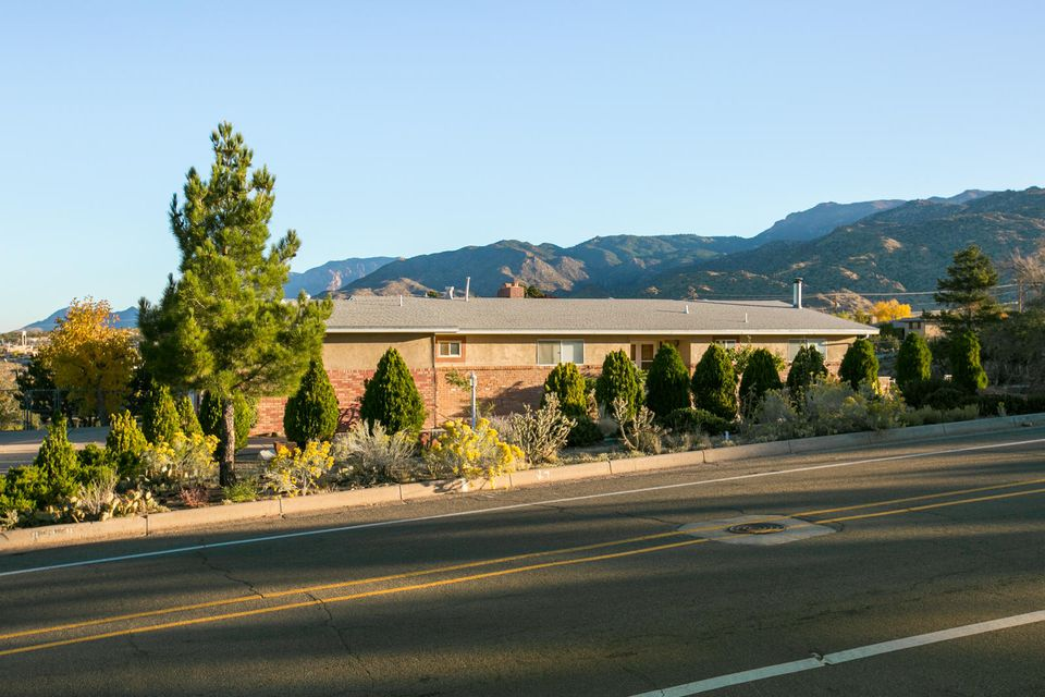 This 3,943 Sq. ft. Four Hills home sits on a large (.32ac) lot with stunning views of the Sandia Mountains.  The light and bright Living Room with fireplace and tongue & groove ceiling opens to the Dining Room and Kitchen which is perfect for entertaining. Very functional Kitchen with ample cabinet space and a pantry for storage. Large Master Bedroom with a 3/4 bath complete with dual sinks. Downstairs you will find the Family Room with another Kitchen, backyard access, and a large bedroom with an attached flex space/office. The outdoors provide Mountain Views and plenty of open space for entertaining. Great location that provides easy access to i40, Kirtland AFB, and Sandia Labs. The 4 lots (totaling 1.99 acres) behind the home can also be purchased (. 22AC, .59 AC, .74 AC, and .44 AC).