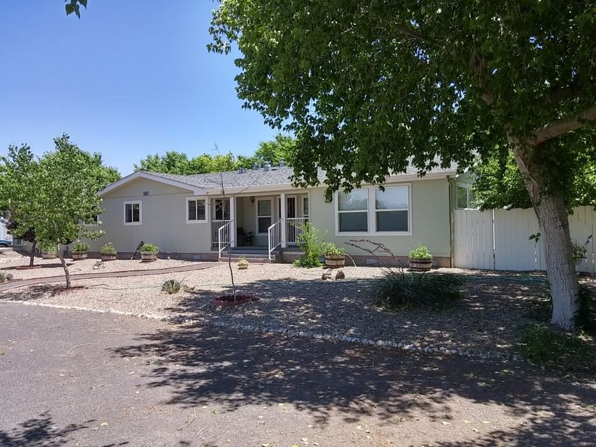 A rural oasis in the Albuquerque south valley. 4.6  acre horse property (7.3 acres total available) Immaculately cared for Karston mfr. home, 3 master suites and an office, site built 27' x 30' finished garage, and 400 sq ft solarium w/ hot tub. Ditch irrigated pastures, fenced and cross fenced with 6' high pipe and wire mesh fencing. 4000 sq. ft. metal barn. 2000 sq ft concrete block stable, 5 stalls, tack room, 15' wide interior aisle. Each stall connects to its own individual corral outside the stable. Stable currently used for storage needs some TLC.  Direct access to miles of popular riding trails along the valley's irrigation ditches. A 2nd parcel, 2.71 acres w/ utilities connected, currently planted in alfalfa, available only as a package deal for add'l $245,000. Bring us an offer!
