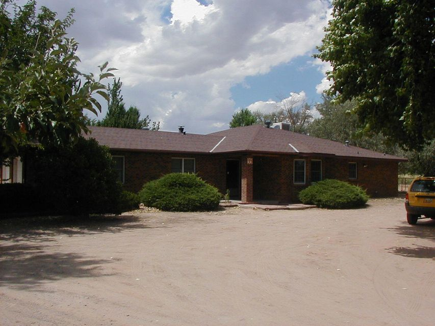 Magnificent Brick Home w/Large Living Room area accented w/ wood burning stove. Experience Country Style living w/tons of mature trees on 1.6 acres. Private Patio area for entertaining many guests w/privacy stucco fence. Huge kitchen area with Bar, Big and Bright Bay window facing early New Mexico sunrise. 3 large bedroom with large walk-in-closets and 3 bathrooms. Anderson Windows. Built in Book Cases. 2 Car Garage with tons of work space. Huge Utility Room. Easy access off paved Rd. Entire property fenced for privacy. Irrigation Well and Private Well on property. Separate Storage building and Huge Workshop area for your projects.