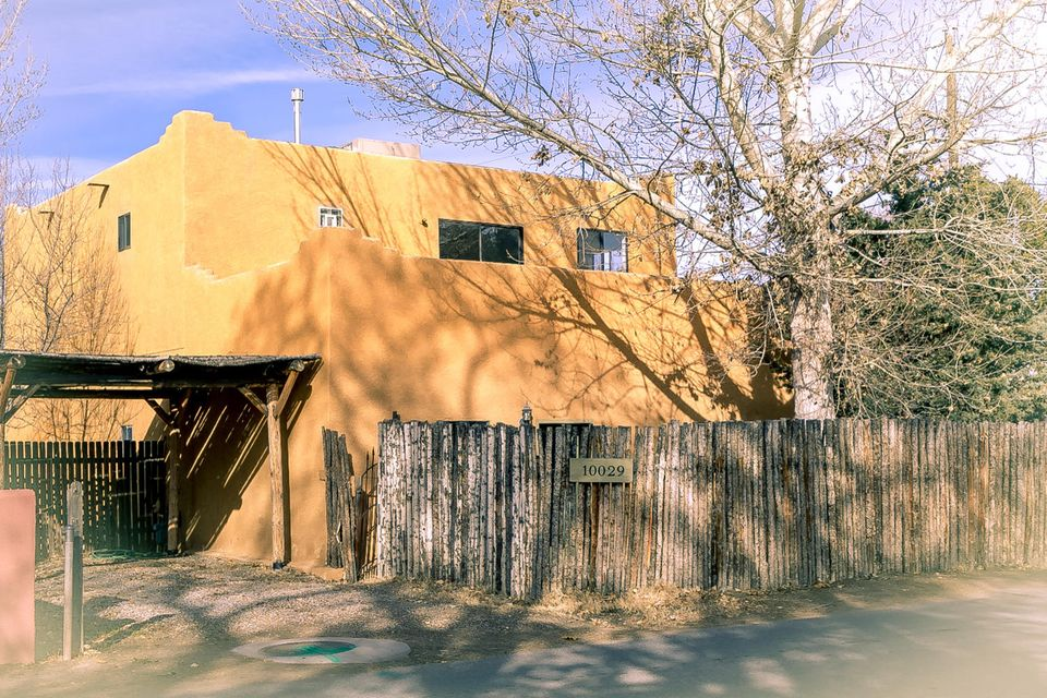 Authentic Pueblo-style adobe home in North Valley historic Alameda neighborhood. This home is loaded with charm including concrete and Saltillo tile flooring, tongue and groove ceiling with vigas and arched doorways. Nice floorplan with two living areas, formal dining room, remodeled kitchen with tile counter tops and back splash, three over-sized bedrooms and three updated full bathrooms. Recent paint and carpet. Fully fenced yard with Coyote fence in front. Large private backyard with screened-in patio, mature trees and pond. Two car carport. Just a short distance from Balloon Fiesta park.