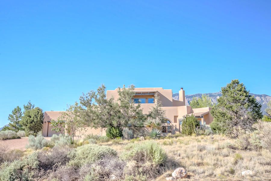 Foothills/The Highlands at High Desert! Premier Area of Custom Homes on Big View Lots! Spacious, immaculate two story contemporary SW style custom on a peaceful, panoramic city sunset & Sandia Mountain view lot! Flowing interior with 6 BRS; 4 MBR Suites possible, 2 on the main level with backyard/patio access & 2 on the upper level with panoramic view deck access. Two separated bedrooms on the main level offer a Jack & Jill arrangement w/private bath. 6 baths,5 full plus one 1/2, greatroom, entertainment/family room, formal dining room, gourmet country kitchen, big service room & a Big 3 car finished garage w/separate/finished workshop w/outdoor access. Manicured exterior w/2 entertainer's patios & 2 view decks. Exposed Adobe 1/2 walls, vertical Vigas Corbels
