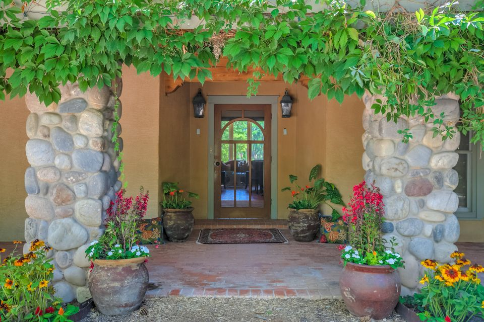 This is a one of a kind, remarkable country estate on seven + acres with loads of room to roam. Check out the VIDEOs in the Photo Section! Located on the South end of Corrales right on the Rio Grande River Bosque. It's just a mile from Albuquerque, but feels like your own quiet oasis in the country. Upon stepping through the front door you will enter into elegance with the Southern style gracious sweeping staircase and towering ceilings. Before you is the main living room with lodge beamed tongue and groove ceilings with stupendous views of the back acreage and river Bosque (woods). The layout of the home is sensational with an extra large kitchen with vaulted ceiling and roomy breakfast nook. The expansive center island is perfect for the head Chef and several mini Sous Chefs. See ''More'