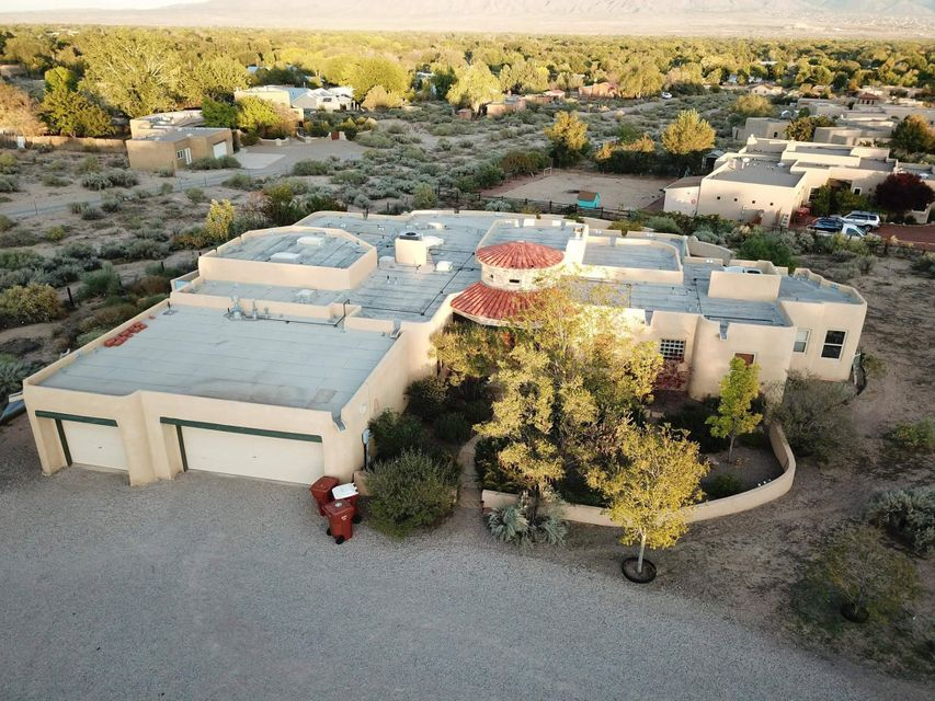 Please come visit our custom home on 1 fully-fenced, gate-accessed acre on the west side of Corrales with a view of the Sandias that, well, you need to see to fully appreciate. 4 BR/3 baths, office, AC, radiant AND forced air heat. New carpet, paint, & TPO roof (w/ 15 yr warranty) - 12/17.  LOTS of natural lighting. Large, open family room wired for surround snd, w/ vigas, T&G ceiling, combo fireplace. Kitchen: new granite countertops, stainless sink & DW, gas stove & 2 ovens (1 convect), bkfst nook overlooks covered, wraparound porch, w/ fruit trees, grass backyard, and fenced garden - all on auto. irrigation.  MBR/bath: fireplace, spa tub, snail shwr, sun room, wlk in closet. Large, multipurpose Rec room w/ INDOOR CLIMBING WALL!  3 car garage. TONS more, but MLS only allows 800 charctrs!