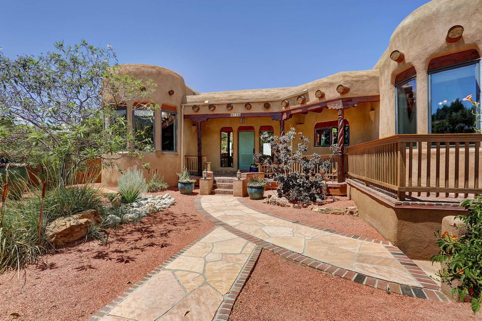 You will be wowed from the moment you walk through the gate of this beautiful custom partial adobe home with breath taking views of mountain and mesas.This home is perfect for many lifestyles and awesome for entertaining.Oversized liv/din welcomes you gleaming tile floors,hand rubbed diamond plaster walls,kiva fireplace,12' wood ceilings, nichos,hand carved corbels,vigas,and more.1600SF of covered verandas offering brick floors surrond the home. Relax over morning coffee and take in the mountain view or enjoy an evening cocktail taking in the glorious NM sunset while the mountain turns pink from your front portal.The heart of the home is large the gourmet kitchen w/top end SS appliances,ample granite counters,custom cabinets,island with prep sink,walk in pantry,breakfast bar,nook,and more