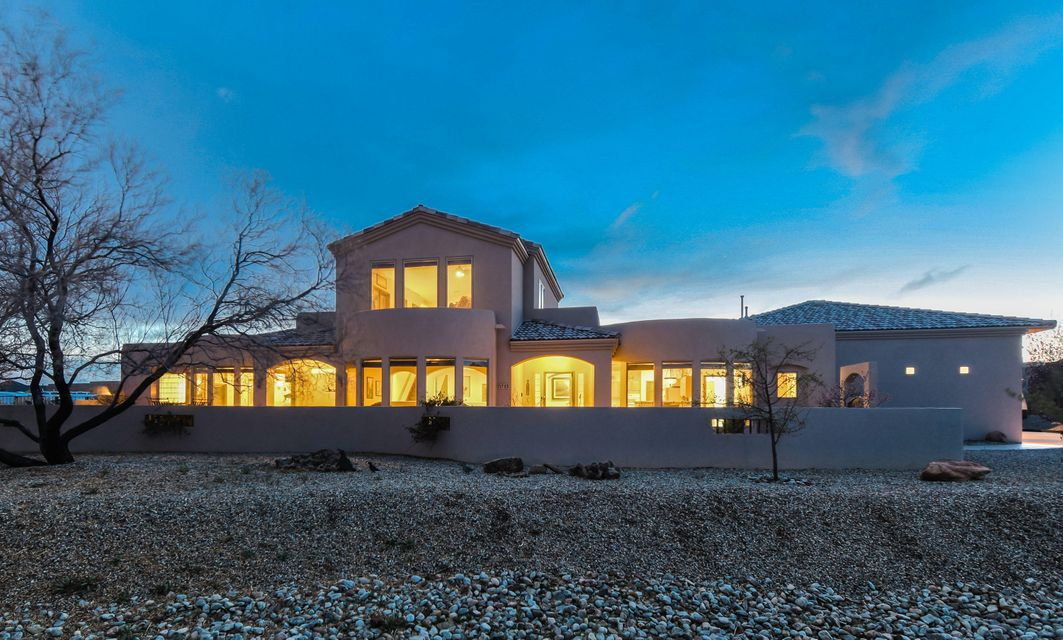 Exquisite custom built home located on a large .75 acre property in the heart of Rio Rancho. Home features 4,485 sf w/ 5 bedrooms, 4.5 bathrooms, 2 living areas a loft and 3-car garage! Gated courtyard entry with open patio. Beautiful kitchen with ample cabinet space, built-in oven and microwave, gas cooktop, huge center island w/ prep sink, seating area, pantry and a breakfast nook! Family room with gas fireplace and updated flooring. First floor master suite with a romantic 2-way fireplace, outside access, a wall of windows with views and private bath. Bath hosts his/hers sinks, vanity area, jetted tub and a custom walk-in shower. Enjoy the huge upstairs loft perfect for a game room, private guest suite, bath and balcony! Outside enjoy the covered patio! RV parking W/ hook up!