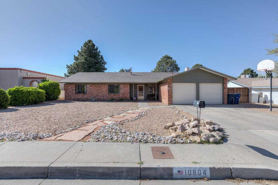 **PRICE REDUCTION, BRAND NEW CARPET AND FRESH PAINT** Lovely home in an established neighborhood, in highly sought after school cluster. This home is conveniently located near shopping and restaurants.  Relish in the views of the Sandia Mountains from your front or back yard!   Fluid floor plan offers 2 separate living areas, 2 dining areas, separate laundry room.  Stay warm in the winter months by your wood burning fireplace with gorgeous surround. Granite countertops in kitchen and bathrooms. Easy care front yard.  Automatic sprinklers and drip system in the backyard allows you to enjoy the foliage without the fuss.  New roof in 2016. Master Cool Evaporative cooler.