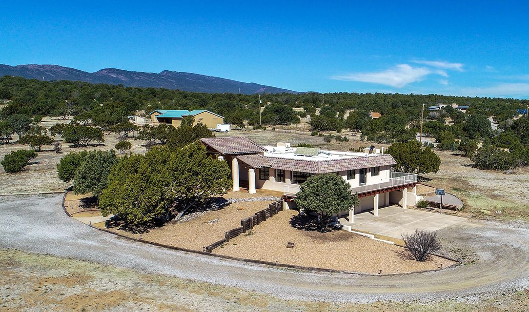 VIEWS*VIEWS*VIEWS*Looking for quiet living, lots of space (5 Acres and 4567 Sq Ft) on the outskirts of Albuquerque, this is the home for you*Only 15 minutes to town*Many updates*Most recently engineered wood floors in the hallway and family room*Past updates include Roof (2012), Water Softener (2014), Septic, Stucco and windows*Private entrance to In-Law/Teen Quarters*Approximately 1775 Sq Ft of living area with Kitchenette, Fireplace, game area with Ping Pong/Pool table that conveys*Bedroom has full bath*Room downstairs could be converted back to a second laundry room*This wonderful 4/5 Bed, 4 Bath, 3 Liv Area has abundance of storage*Enjoy the great views of the South Mountains and magnificent Sunrises and Sunsets*Wrap-around deck*Master bedroom has private patio*All 5 Acres are fenced*