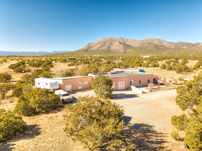 Don't miss out on this Custom-built, single level, New Mexico Territorial style home located on 6 acres! This well-maintained home features living room vigas, bay windows, and tile flooring throughout. The kitchen has maple cabinets and also an island with a vegetable prepping sink. The formal dining area opens into the family room creating a large open space for entertaining. There are covered porches front & back, as well as an oversized 2 car garage and RV parking. The attached guest house has it's own separate entrance and it's own oversized garage! Schedule a showing today and see everything this home has to offer!