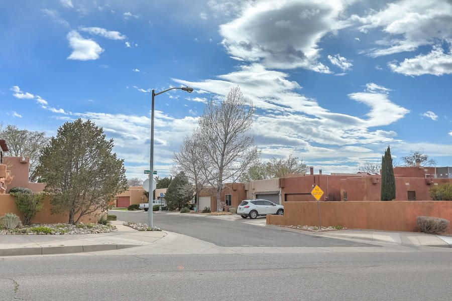 Sought after Kachina Hills Subdivision; This former model home is nestled near the base of the Sandias, close to parks, the Open Space and nature trails, where you can view spectacular sunrises, sunsets and the city lights. This patio home is located on a cul-de-sac in the Cambridge Park neighborhood with other pueblo-style patio & single-family homes on view lots. This one-level, contemporary-styled home is flooded w/natural light & well suited for entertaining. The bedrooms are secluded away from the entertainment area! Two-car garage w/ ample storage space. Manicured front & backyards w/ mature landscaping. The back yard offers a covered patio w/ both peaceful seclusion & panoramic views of the Sandias, Jemez Mountains, Mount Taylor and the Valley below.**new  countertops available**!