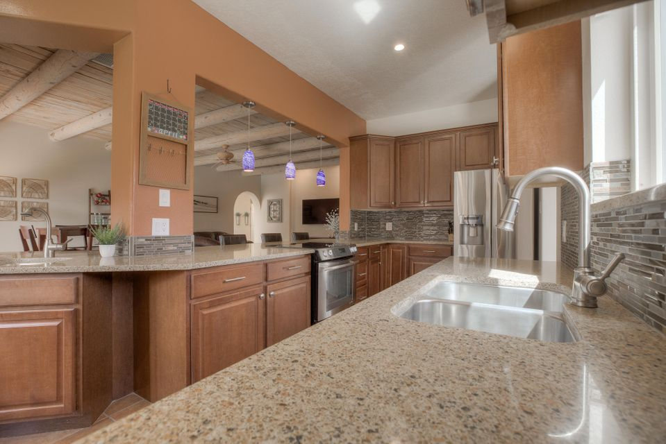 Don't miss 3D tour in Virtual tour link!! Beautifully remodeled North Valley home near the Bosque! 2 living areas: 1 with 16' celings and two way gas log fireplace to formal dining room, 1 with w/wood viga ceiling and open to the completely remodeled kitchen. Large master suite with separate shower, dual sinks, private commode, and large walk-in closet. Secondary bedrooms have big closets with built in storage. Large backyard with shade tree, 2 patio areas, and side access for storage of your RV/trailer/toys. Refrigerated air plus new flooring, paint, windows, stucco, cabinets, counters, lighting, and landscaping! This one is move in ready, with modern updates and SW charm!