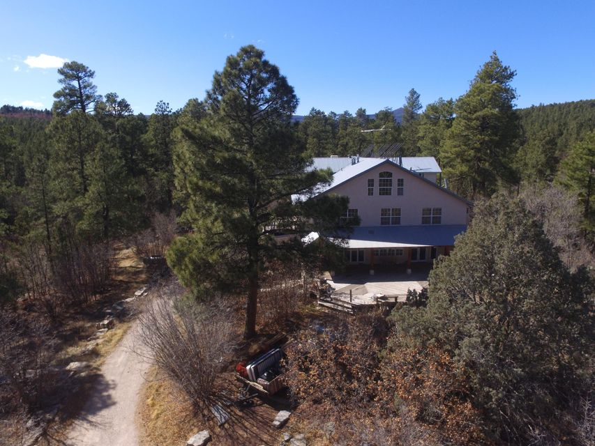 Get out and see this gorgeous mountain property today! The main house is a 6223sqft fixer upper waiting to be completed the way you want it. This is your chance to get in a luxury home at a fraction of the price! The expansive decks and balconies are surrounded by tall pines, native bushes and flowers. Detached guest cottage/cabin will be great for your guests. Owner financing and trades considered! Get out and see this one before it's gone!
