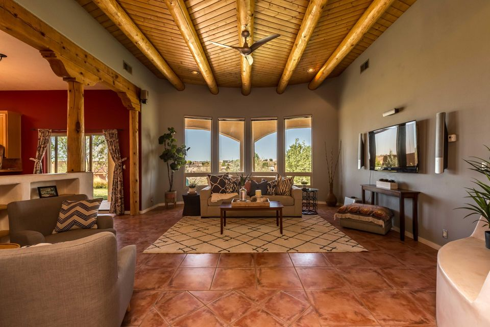 This contemporary Pueblo style home offers an open concept floorplan, an abundance of natural light, and custom Southwest accents such as wood viga ceilings and a kiva fireplace accented with nichos.  From the private patio near the grape arbor, watch the sunset across the serene New Mexico desert scape of this spacious half-acre property or enjoy the panoramic view of the Sandia mountains from the front yard! Comfortable living abounds with the spacious master suite complete with walk-in closets, his & her sinks, and garden tub. Energy efficient features include Anderson thermal windows and radiant heat.  With over 2,000 square feet of living space, 4 bedrooms, 2 1/2 bathrooms, and 2-car garage this home is ready for YOU to come see today!