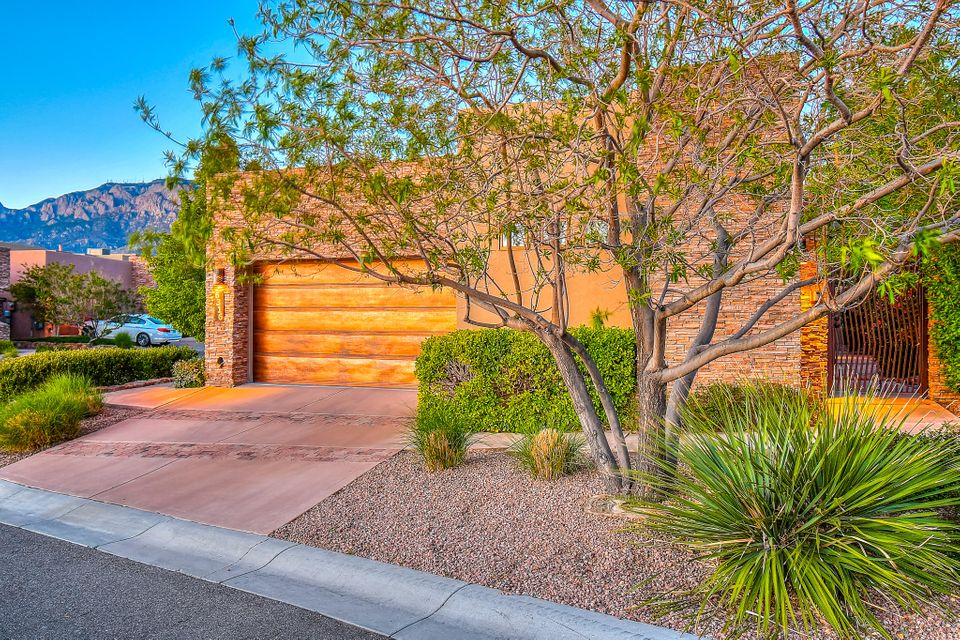 This custom Rutledge home is truly one of a kind.  You'll enjoy an exquisite unobstructed view of the Sandia Mountains from the large living room window.  The Kitchen boasts Wolf appliances, granite counter top, Sub Zero fridge and freezer, wood floors, custom cabinets, and a great bar area.  There is a cozy fireplace in the living room bordered with stacked stone accents.  The master has backyard access, a spacious bathroom area, and great walk in closet space.  The bonus basement has a finished bathroom and could be great as an office, theatre, or an extra bedroom if desired. In the backyard you will find 2 lovely water features, a gated entrance to the front door courtyard area, and very easy maintenance landscaping.  This home truly has one of the best views in the entire neighborhood!