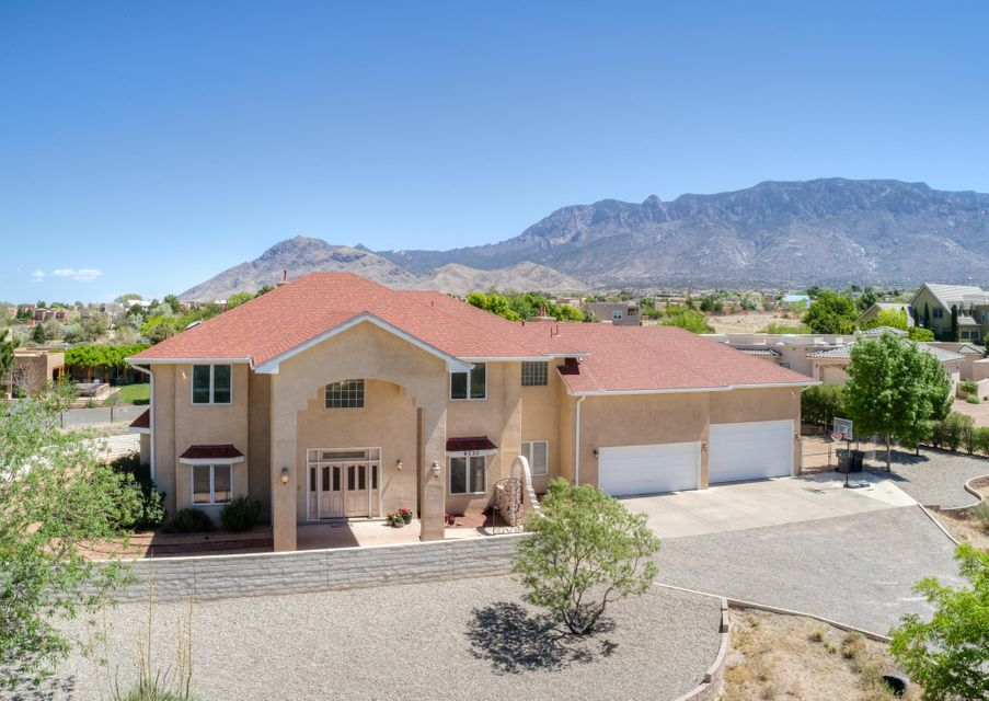 This stunning custom 4350 sqft home nestled on .89 acres is an unbelievable deal in one of Albuquerque's most sought out areas! This large 5+ bedroom home has plenty of space for everyone. The beautiful & spacious kitchen is a chef's dream that features high end appliances, granite countertops & a large center island. The 5 over-sized bedrooms all have their own attached bathrooms & generous walk in closets. The large owners suite is truly special w/ a gas log fireplace, sitting area, & breathtaking views off the private balcony. The huge over-sized 4-car garage is every mans dream garage w/ an RV door, workbench & high ceilings. Extras include a new roof, 3 gas log fireplaces, radiant floor heating, central vac, tons of storage, beautifully landscaped backyard w/ separate dog run & MORE!!