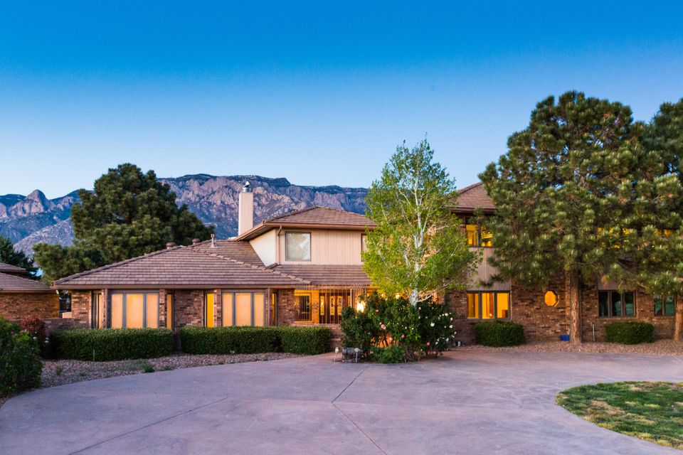 This beautiful custom estate by Rutledge sits on about 2 acres of immaculately landscaped land.  The views of the Sandia Mountains from the grounds are impeccable!  You'll enjoy the updated slate flooring, new kitchen with beveled edge granite, custom cabinets, and custom metal range hood. The living room is open to the 2nd floor with high ceilings, a cozy fireplace, and lots of windows to enjoy the view. The large master also has a fireplace, new laminate wood flooring, and his-her walk in closets.  In the master bath you'll enjoy a separate tub, walk in shower, towel warmer, and more! There is no lack of space or storage with the 5 bedroom 5 bathroom home!  There is also a loft type game room. The 8 car garage, one with a pit, and 40'RV garage. This gated estate is truly lovely!