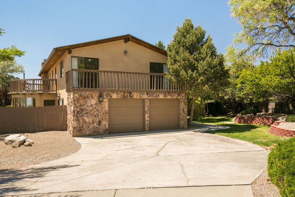 Located at the base of the FOOTHILLS in Glenwood Hills you will find this beautiful custom home. This home offers fantastic panoramic views of the City & Sandia Mountains. Spacious Family Room off of the Kitchen with a gas log fireplace with stone surround and built ins. Gracious formal Dining Room with teak laminate flooring and opens to the beautifully remodeled Kitchen with hickory cabinets, new counter tops, custom lighting, and stainless appliances. Private Master Suite with a spa like bath and private deck for taking in the views. All upstairs bedrooms offer deck access with stunning views. The private, park like backyard offers is a fenced oasis of grass, fruit trees, rose bushes and mature trees. The front yard offers perennial flowers and a herb garden.