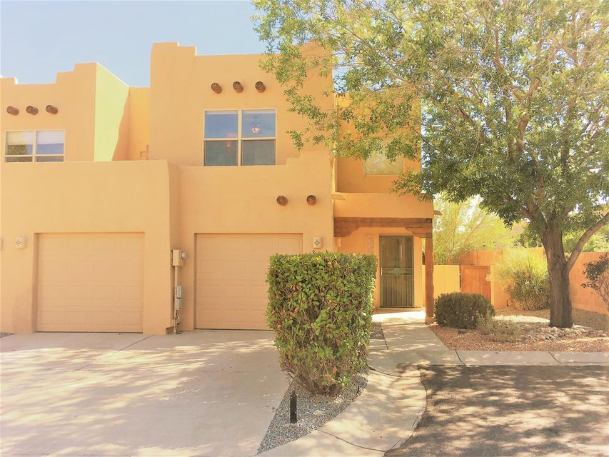 Charming pueblo style home located in gated community with direct access to the Bosque! New granite in the kitchen, new carpet, new wood floors, gas fireplace and refrigerated air. Spacious layout with soaring ceilings. Huge loft which can be used as an office, den, playroom, etc. Landscaped yard with private patio in the back.  Conveniently located near restaurants, gym, shopping and much more! REC available!!!