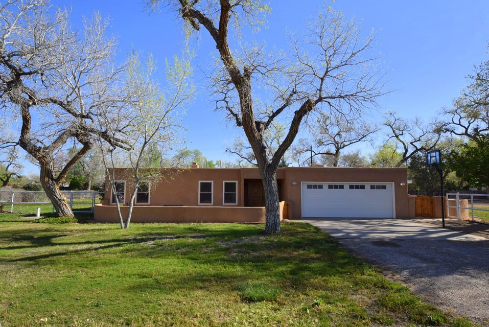 Back on market! Beautifully updated home located east of the river on picturesque road with mature cottonwood trees. Courtyard and enclosed entrada welcome you home to this custom pueblo. Gorgeous kitchen with granite countertops, new cabinets, and Capital 6 burner culinary range. Kitchen opens to living area which has a custom plastered fireplace. Second living area boasts a lovely kiva fireplace. New TPO roof Aug 2018, new alder wood doors throughout, refinished oak floors, new carpet in bedrooms. Other recent updates include upgraded power panel, finished garage, pre-wired for refrigerated air, and sprinkler system that runs off irrigation well. Situated on 1 acre, this home offers space for all your hobbies, family gatherings and horses.
