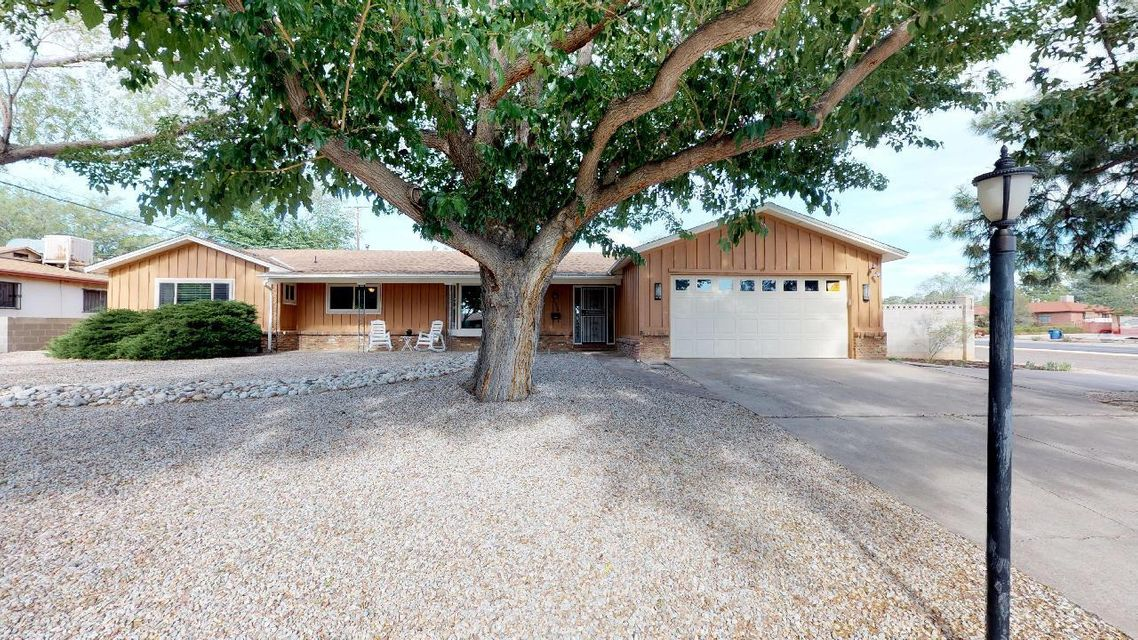 Just in time for summer!  This appealing single-story home in the NE Heights offers hours of fun in the sun on an oversized corner lot with gorgeous yard and pool!  The well-designed, east facing backyard features a covered patio, large yard with garden areas and fruit trees and the refreshing pool fenced and off to the side.  Only a block to La Palomita Park and close to Sandia HS!  This four bedroom home offers space for everyone, with 2 living areas, large eat-in kitchen, formal dining room, 2 bathrooms, 2 car garage with storage/work area plus a bonus bar/storage area with sink off the family room. Open floor plan is great for everyday living, cozy evenings by the brick fireplace or ideal for entertaining with natural flow inside to out! Hurry to call this house your home!