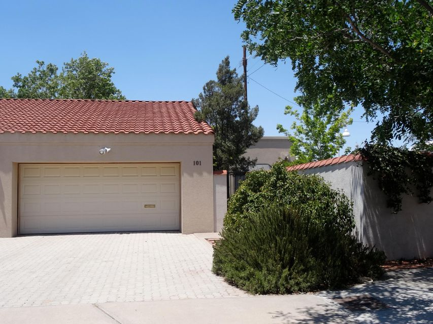 Fabulous One Story Town Home at the entrance of the Albuquerque Country Club.  These townhomes rarely come available. Two master suites with ensuite full baths. Open Concept Living room/dining room. Automatic Privacy Screens on glass doors to the back yard.  Shady out door space in the front and back.  This particular unit has out door access into the back yard.  Don't miss the opportunity to live in this very desirable neighborhood.  NO HOA FEES.