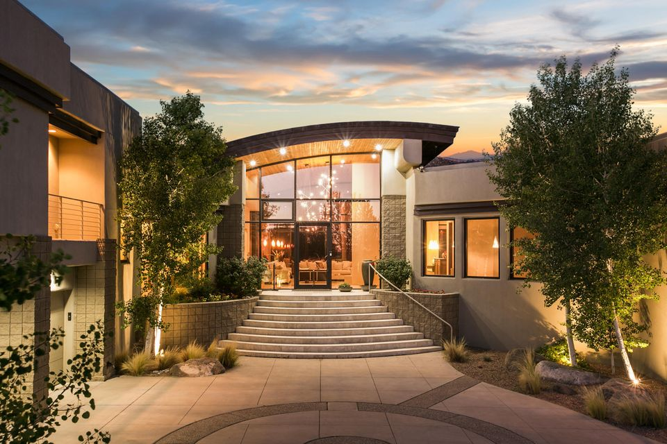 Dynamic contemporary home designed with multiple levels to capture remarkable views of the Sandia Mountains and the City Lights. Clean & classic finishes create the perfect backdrop for stunning contemporary architecture which is sexy, yet warm and inviting. This home is beautifully situated on a premier Estate Lot in High Desert with inviting outdoor living spaces and a backyard big enough to accommodate a pool. Each bedroom has it's own private bath, and a flexible floorplan affords a variety of options. Luxurious finishes such as floor to ceiling windows, travertine flooring, beautiful custom doors, furniture grade cabinetry, and rich granite define this lovely home. Kitchen features a Wolf and Subzero appliance package and a huge pantry. Incredible value for a wonderful home