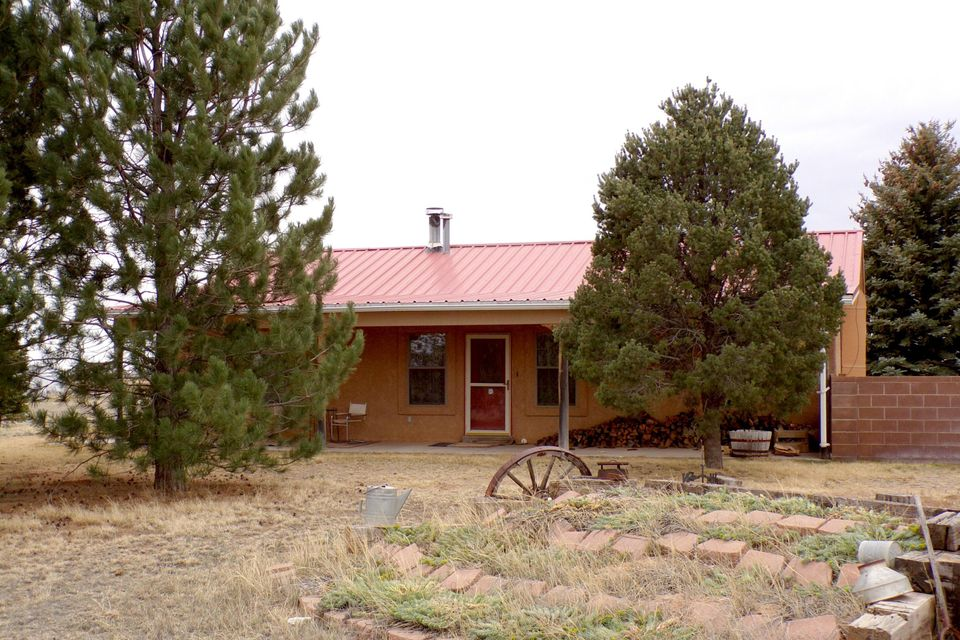 This central New Mexico horse property on 5 acres is near Moriarty with easy access to I40. Albuquerque is about 30 minutes away and Santa Fe about an hour. This property has it all with every man's dream of a large shop with two roll-up doors, horse barn, stalls and corral. The home has 3 bedrooms and 2 baths, large living and dining rooms and a style country kitchen. The landscaping is lovely with a walled back yard and sun porch for watching the sun go down over the Sandia Mountains. This is your rural lifestyle yet so close to the city.  Home is also offered with an additional 15 acres.  Refer to MLS listing # 916182.