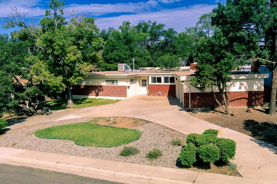 L@@K at this spacious home in high demand area for services, transportation, and UNM. This single level home features 2 living areas, 3 spacious bedrooms and 2 bathrooms. BONUS is an inground pool located in enclosed detached building. Pool has been serviced and is in good working condition. Enjoy the pool all year round with family and friends. Entire interior has just been painted. This retro style home is a perfect project for updates which is very common for the area. Long term investment opportunity awaits for the new buyer. Double front entry through total enclosed porch gives endless decorative possibilities and is access to oversize garage with workshop space and lots of shelving. Circular driveway for extra parking.