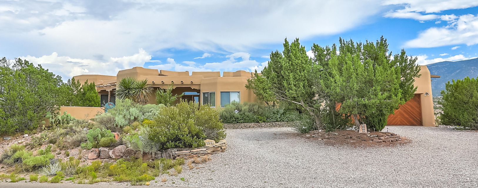 This is the quintessential Placitas property!!! Perched high on a hill w/  spectacular VIEWS of the Sandias AND sunset views! Glorious front and back courtyards. This custom southwestern Ashe home on 2+ acres has elegant touches and warm, New Mexican charm including latilla ceiling with vigas, arches, exposed wood headers, corbels and wood rope columns, tile floors, clerestory windows, & adobe accent walls.  Open floorplan for light & bright spaces.  Living area has large windows to take full advantage of the beautiful scenery, fireplace with nichos & banco, and access to back patio.  Gracious kitchen with exquisite custom cabinetry w/ inlays, large island with vegetable sink, breakfast nook and patio access.  Spacious master with spa like ensuite including jetted tub & separate shower.