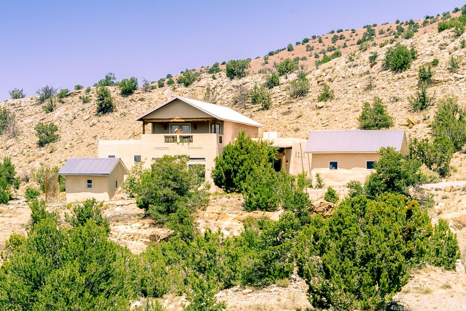 This beautiful, tranquil Northern New Mexico style home is located on 1.9 acres in the Village of Placitas. Open concept with great flow and amazing views of the Sandia Mountains and western mesas! Custom touches throughout - lighted nichos and built-ins with seed-glass doors, beamed pine tongue-and-groove ceilings, custom plaster walls, stacked stone fireplace with Artisan gas insert, chef's kitchen featuring granite counters, deep sinks, custom tile backsplash, s/s appliances, gas cooktop, double ovens and lots of storage in knotty hickory cabinetry w/ under cabinet lighting. Master-on-main with spacious en-suite bathroom; 2 bedrooms upstairs w/ Jack & Jill bath and view balcony. The home and 2 straw-bale constructed out-buildings are enhanced by natural and xeric SW landscaping.