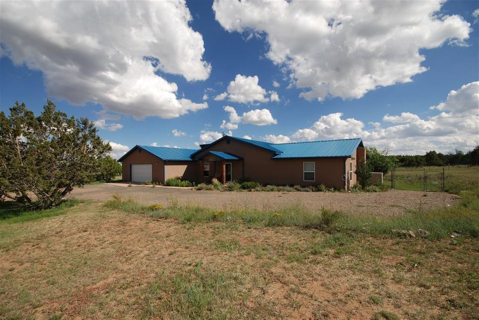 Assumable VA $223,000 at 3.62%PITI $1300. True country home.  Level useable 2 cross fenced acres. Polished concrete floors, large great room with efficient wood stove.  Master on one side with private bath, 2 huge bedrooms on other side with shared bath.  Vaulted wood ceiling. Large kitchen with center island. Greenhouse across the back.15 raised beds.. Water heater, boiler, softener 2014.  Sunny patio out back, shady covered porch out front. Nice neighborhood, internet, good well and septic. Generac propane generator as back up. Evaporative cooler vents in all rooms, radiant floor heat.  Solar system not functioning, can be removed.Metal roof, stucco exterior. Little Hogan out back with wood stove.  Well produces 1500 gallons per day, 45000 gallons per month.