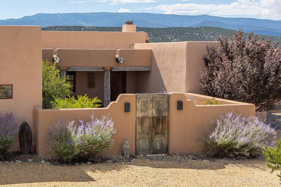 Space and artistic design take on a whole new meaning in this stunningly executed, Green-Built home that exemplifies the best in Southwestern architecture. You'll glory in the majestic mountain vistas this enchanting pueblo offers in The Overlook, an exclusive, gated community located along the Turquoise Trail National Scenic Byway* Inviting courtyard entry w/antique Mexican gates*e-crete block construction (green, fireproof, insect and mold resistant, high R value and soundproof)*stained concrete flooring*diamond & clay plaster & clay-painted walls*18'' standing-dead spruce vigas, latillas*Viking Professional Series appliances, custom Alder cabinets and doors*HOA offers gated/guard/concierge service including a sophisticated camera system, Community Center, pool & spa* Amenities attached.