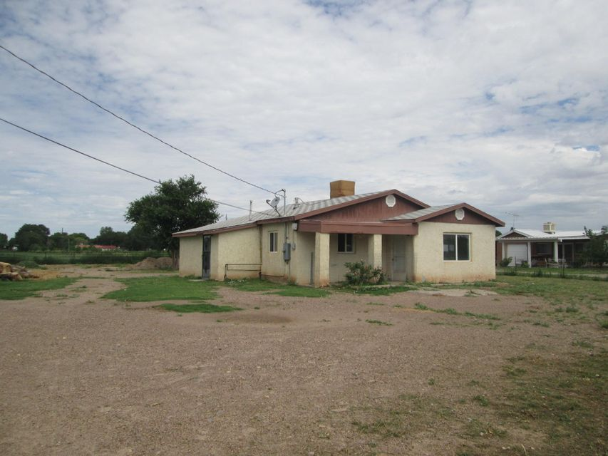 Lots of business possibilities with this 2 bedroom 1 bath home with an office on a full acre.  Updates include newer double pane windows, updated electric service, 125 ft. of highway frontage on Hwy 314 in Los Chavez.  Property includes a 15x30 ft. garage, a 24x30 ft covered pen area with several attached stalls. There is a .75 acre fenced pasture.  Entire acreage is  1.34 and  includes a 30' road easement on the south side of the property. Gated entry and fully fenced. This is the perfect place for a variety of possibilities.  Take a look!  Owner will consider financing with NM Real Estate Contract.