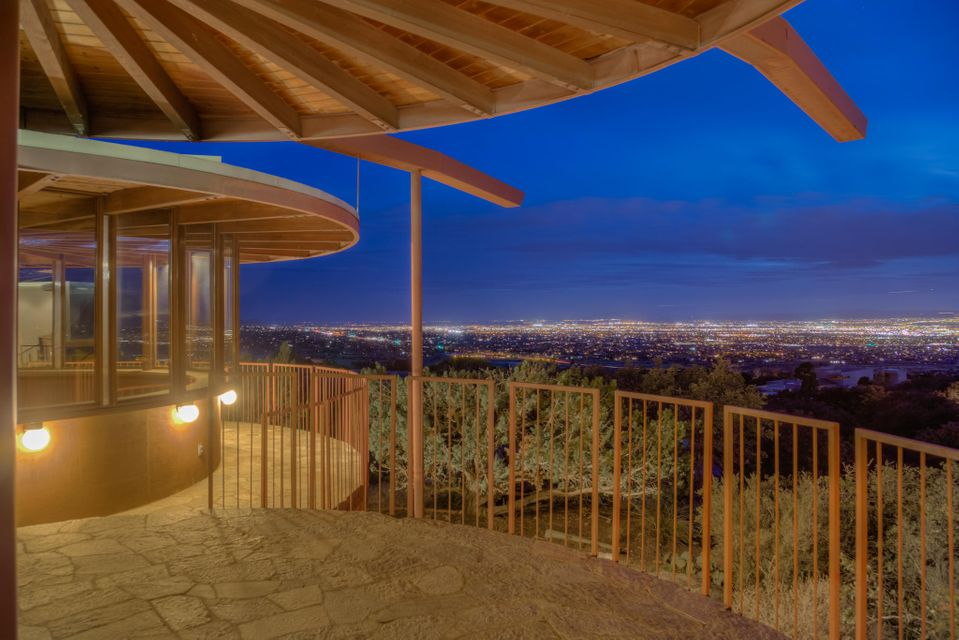 Award winning Bart Prince design in North Sandia Heights with FOREVER views. This home was designed & built for his father. A real labor of love! Multilevel plan with exposed beams, lots of light including skylights and full walls of windows. An architectural marvel. Terraces and decks on all sides joining the outside and inside spaces. Contemporary design, inside and out. Incredible architectural detail. Boulders used from site for the custom fireplace and left in place in the entry & MBR. Modern kitchen with granite counter tops. 2 bedrooms with Jack & Jill bathroom separated from Master. Kiva style office with windows all around. Outside wrap around patios for sunset & city light views and, in front, a view of the Sandia Mountains. Almost 1 acre lot bordering Open Space & 3 car garage