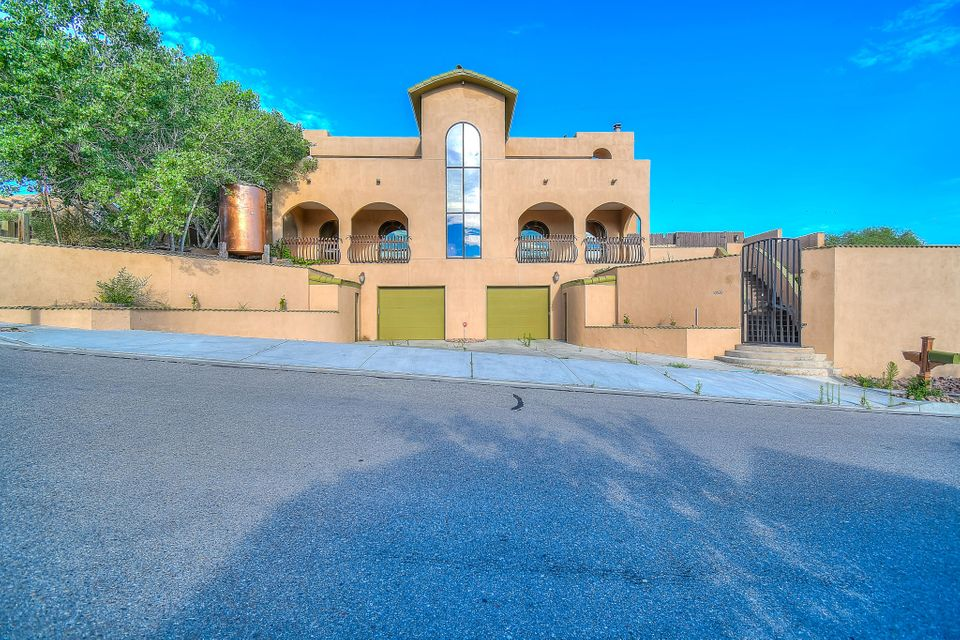 Gorgeous Custom Home!! Breath Taking Views of the Sandia Mountians! Working Elevator!  4 to 5 Bedroom!  Large Chef Kitchen with Bar! 60' Gas Stove and Custom Cabinets throughout!  3 Refrigerated Air Units/Heater! Cozy Living Room with Fireplace!  All Brick Flooring throughout! Over sized Master suite of 1000 sq ft with wood burning fireplace! Plus Coffee Bar!  Large Master Bath with Garden tub and Double Sink!  Home also has a Central Vacuum unit! Romero and Juliet balcony! 3 cherry trees and Fuly landscaped!  Bonus room in garage for Man cave! Its a Must See!