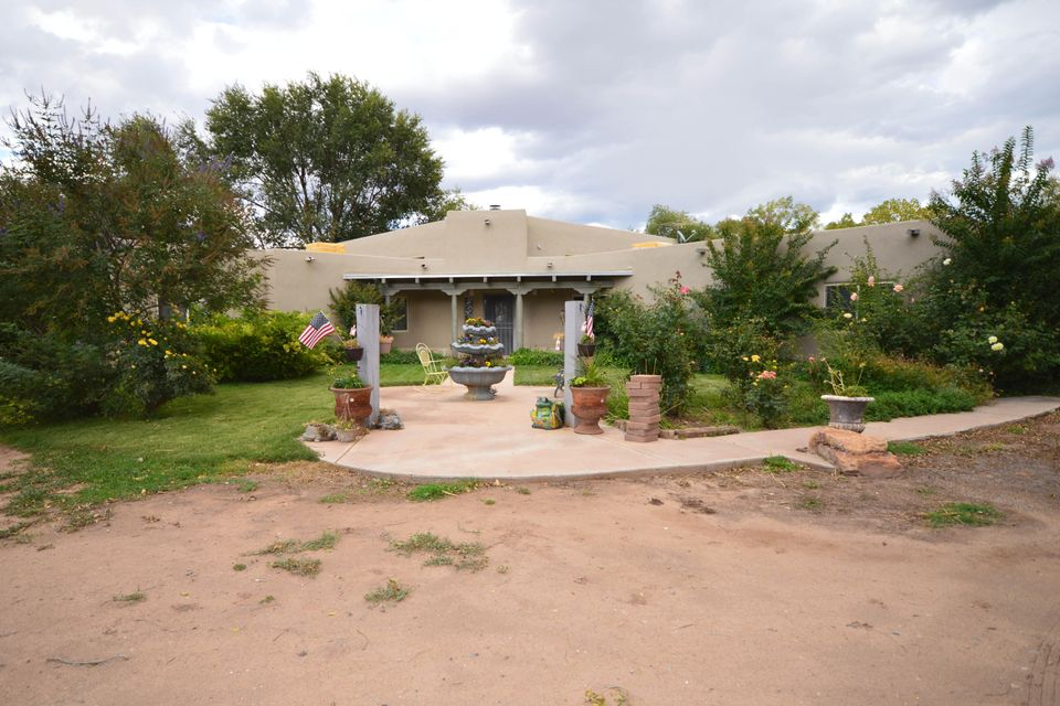 Located on a quiet north valley street, this beautiful southwest home has a huge great room with high wood ceiling with vigas, custom kiva fireplace and built-in entertainment center. Kitchen has double ovens, gas cook top, microwave, built-in refrigerator, island, large pantry and breakfast nook. Spacious master suite has fireplace, two closets and bath with dual sink vanity, garden tub and separate shower.  Fourth bedroom and bath is separate from other bedrooms ideal for guest or in-laws. Backyard has large covered patio with fireplace, covered storage area and fenced yard for horses and other animals.
