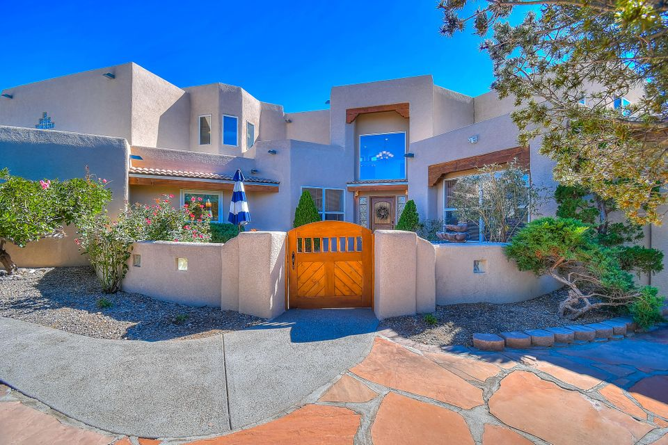 Forever views of glowing balloons, colorful mountains, and endless blue skies! Open floorplan with walls of windows and skylights. Chef's kitchen has island, pantry, granite, stainless, recessed, pendants, and more. Master retreat features a huge walk-in, jet tub, separate vanities, and a private porch w/ inspiring views. Fifth room makes the perfect office, studio, or additional bedroom. Going outside? This home has 4 covered porches and patios, chiminea, bancos, courtyard, basketball court, blooming vegetation, and much more. Custom pool/hot tub w/waterfall is like a blue lagoon from a movie set. No messy power lines-all buried utils. Hidden solar panels pay most of your energy bill (no leases involved). Entertain a crowd or cuddle up in privacy with a good book... this home has it all!