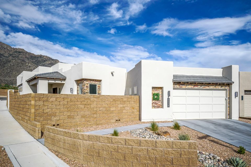 This extraordinary home & brilliant floor plan includes beautiful and spacious living areas with well thought out details. A wall of windows offer Sandia Mountain views from the living room. A chef's dream kitchen has Bosch appliances, 6 burner cooktop, Subzero fridge & tons of storage and counter space & an island with a custom butcher block top. Beautiful tile & wood flooring, granite & quartz counter tops & skylights for natural light throughout. Spacious master suite has a beautiful bathroom & huge walk in closet. The private backyard is perfect for entertaining, relaxing after a long day or taking a swim in the sparkling lap pool. It's heated for year round use & has a walk on cover for safety. Enjoy views of the city lights from the front courtyard in the evening.