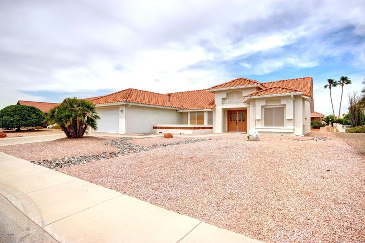 This home welcomes you with an inviting courtyard and a double-door entry.