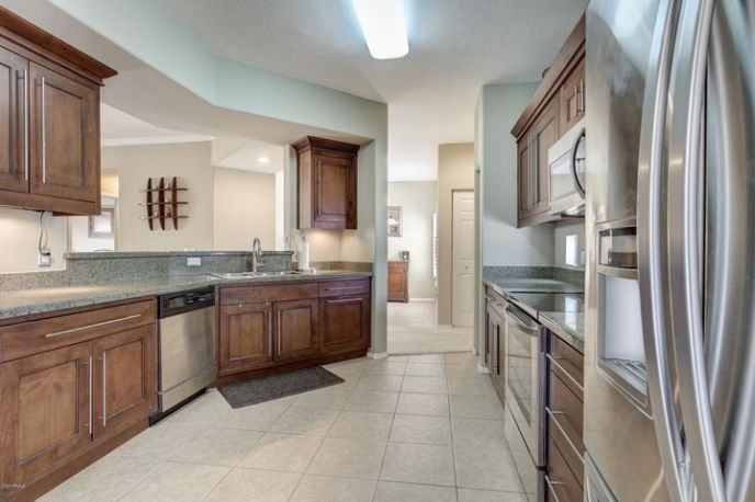 Large kitchen with granite counters and stainless appliances.
